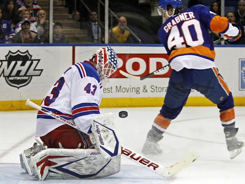 New York Rangers goalie Martin Biron (43) blocks a shot by New York Islanders right wing Michael Grabner (40) in the second period of their NHL hockey game at Nassau Coliseum in Uniondale, N.Y., Friday, Feb. 24, 2012. (AP Photo/Kathy Willens)