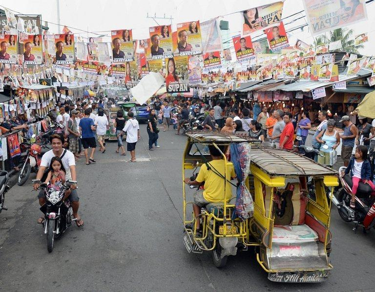 Motorists drive past election posters outside a polling station during mid-term elections in Manila, on May 13, 2013. People are going to the polls to choose thousands of local leaders plus national legislators in what is seen as a referendum on the presidency of reformist Benigno Aquino