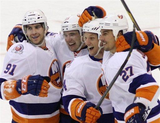 From left to right, New York Islanders' John Tavares, PA Parenteau, Mark Eden and Milan Jurcina celebrate their 2-1 NHL overtime win against the Ottawa Senators in Ottawa, Ontario, Friday Feb. 3, 2012. (AP Photo/The Canadian Press, Fred Chartrand)
