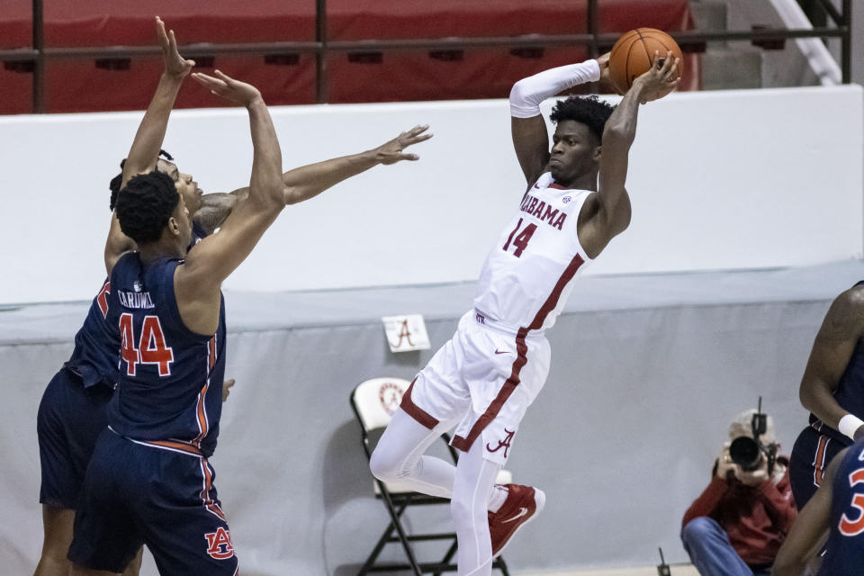 Alabama guard Keon Ellis (14) passes the ball as Auburn center Dylan Cardwell (44) defends during the first half of an NCAA college basketball game Tuesday, March 2, 2021, in Tuscaloosa, Ala. (AP Photo/Vasha Hunt)