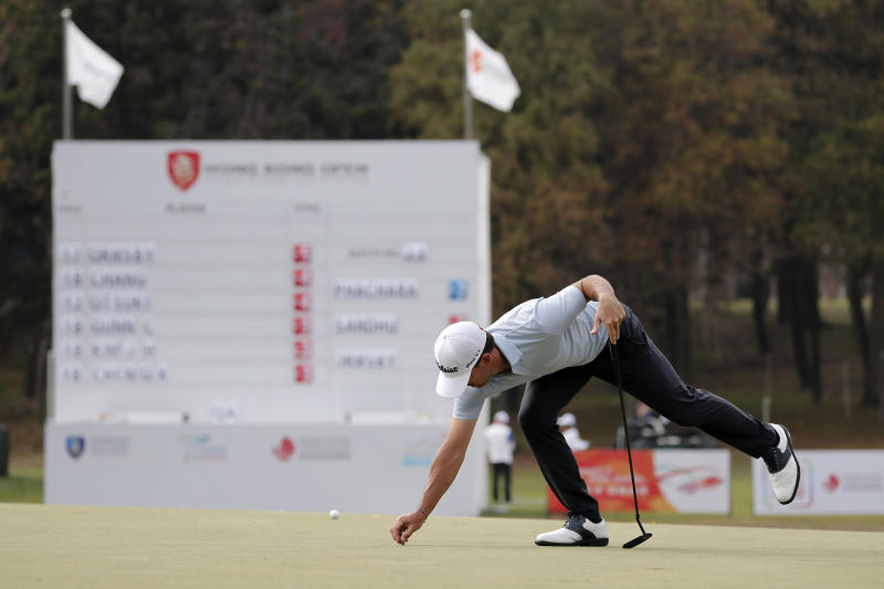 Wade Ormsby of Australia clears for his putt on the 18th hole during the Hong Kong Open golf tournament at Fanling Golf Club in Hong Kong, Thursday, Jan. 9, 2020. (AP Photo/Andy Wong)