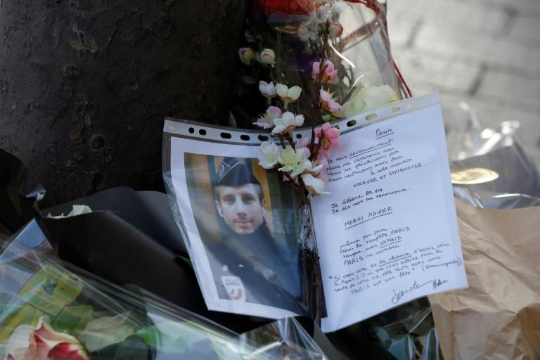 A photo and a letter displayed at the site of a shooting on the Champs Elysees which left one police officer dead and wounded two others