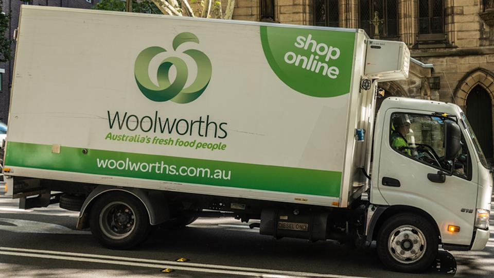 Pictured is a Woolworths delivery truck stopped in a street.