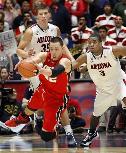 Utah's Jason Washburn (42) dives for the ball in front of Arizona's Kevin Parrom (3) and Kaleb Tarczewski (35) during the second half of an NCAA college basketball game at McKale Center in Tucson, Ariz., Saturday, Jan. 5, 2013. Arizona won 60-57. (AP Photo/Wily Low)