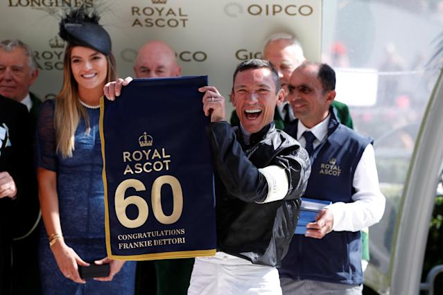 Horse Racing - Royal Ascot - Ascot Racecourse, Ascot, Britain - June 21, 2018 Frankie Dettori celebrates with a banner commemorating his 60th Royal Ascot win Action Images via Reuters/Paul Childs