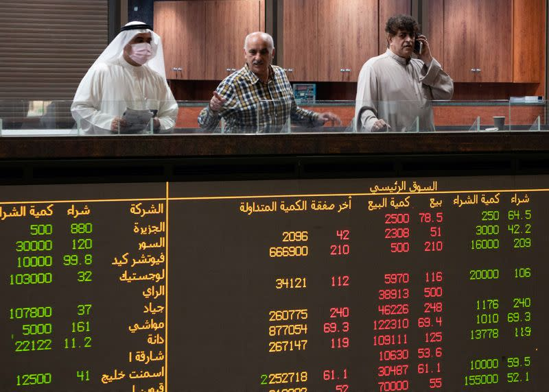 A Kuwaiti trader wears a protective face mask, following the outbreak of the new coronavirus, as he stands on the upper floor since the lower main hall is closed to traders at the Kuwait Boursa stock market trading in Kuwait city