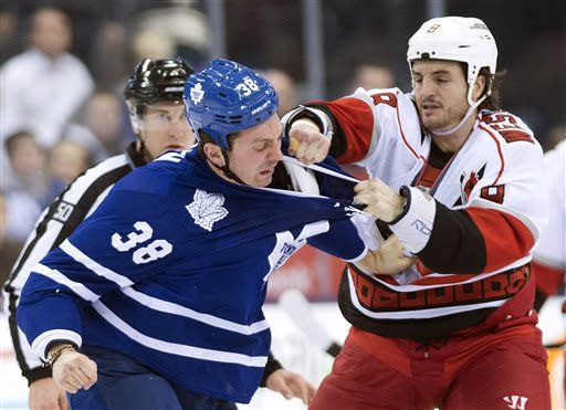 Toronto Maple Leafs forward Frazer McLaren, left, fights with Carolina Hurricanes foroward Kevin Westgarth, right, during the first period of an NHL hockey game in Toronto on Thursday, March 28, 2013. (AP Photo/The Canadian Press, Nathan Denette)