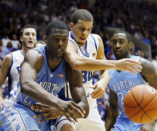 North Carolina's Harrison Barnes, left, and Justin Watts, right, reach for the ball against Duke's Seth Curry, center, during the first half of an NCAA college basketball game in Durham, N.C., Saturday, March 3, 2012. (AP Photo/Gerry Broome)
