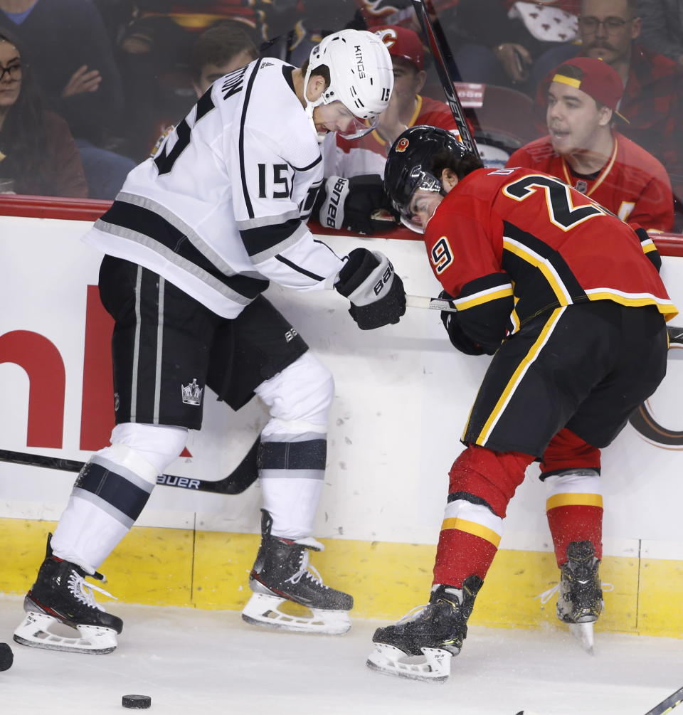 Los Angeles Kings' Ben Hutton, left, and Calgary Flames' Dillon Dube work for the puck during the first period of an NHL hockey game Saturday, Dec. 7, 2019, in Calgary, Alberta. (Larry MacDougal/The Canadian Press via AP)