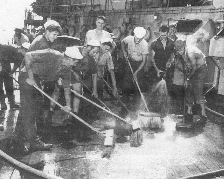 A group of men brushing and cleaning the deck of a ship to try to remove the radiation fallout from an atomic explosion.