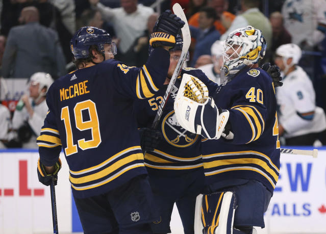 Buffalo Sabres defenseman Jake McCabe (19) and goalie Carter Hutton (40) celebrate the team's 4-3 victory against the San Jose Sharks in overtime in an NHL hockey game Tuesday, Oct. 22, 2019, in Buffalo, N.Y. (AP Photo/Jeffrey T. Barnes)