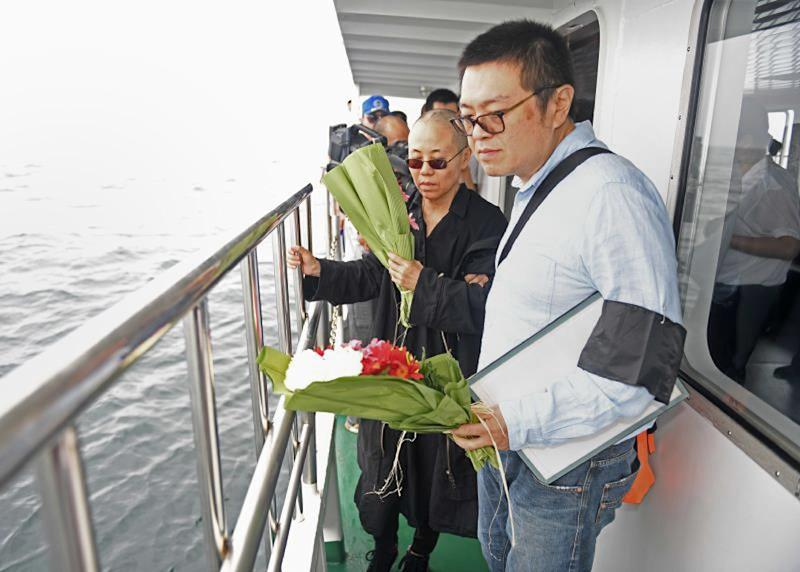 This handout file photo provided by the Shenyang Municipal Information Office shows late Nobel laureate Liu Xiaobo's wife Liu Xia (L) and her younger brother Liu Xiaoxuan, holding flowers as they scatter Liu's ashes at sea off the coast of Dalian on July 15