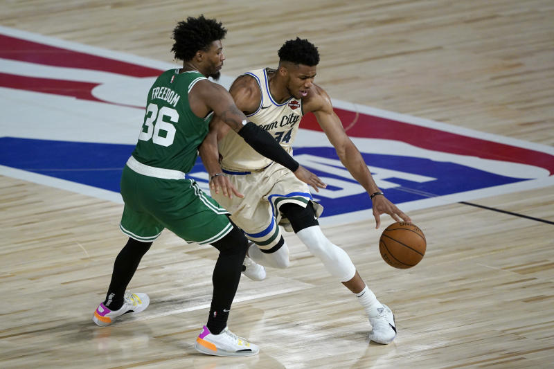 LAKE BUENA VISTA, FL - JULY 31: Giannis Antetokounmpo #34 of the Milwaukee Bucks, right, drives around Marcus Smart #36 of the Boston Celtics during the second half of an NBA basketball game Friday, July 31, 2020, in Lake Buena Vista, Florida. NOTE TO USER: User expressly acknowledges and agrees that, by downloading and or using this photograph, User is consenting to the terms and conditions of the Getty Images License Agreement. (Photo by Ashley Landis-Pool/Getty Images)