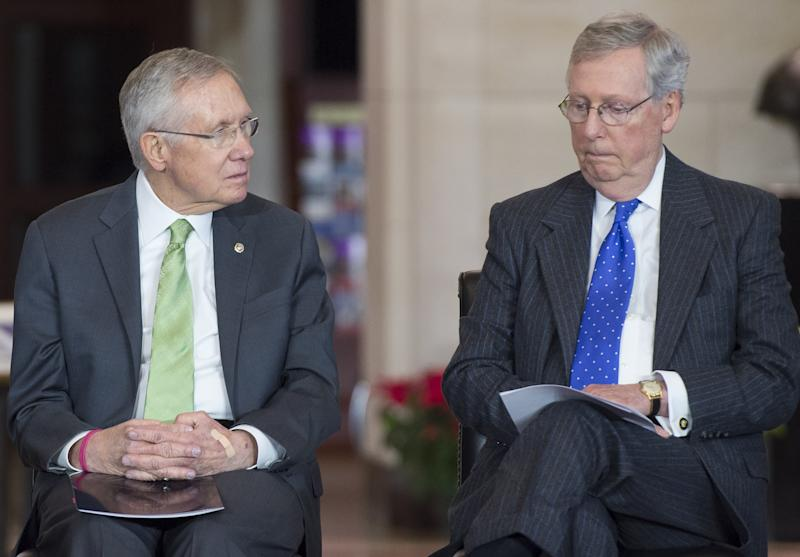 US Senate Minority Leader Mitch McConnell (R) and Senate Majority Leader Harry Reid attend a ceremony at the US Capitol, Washington, DC, December 10, 2014 (AFP Photo/Saul Loeb)