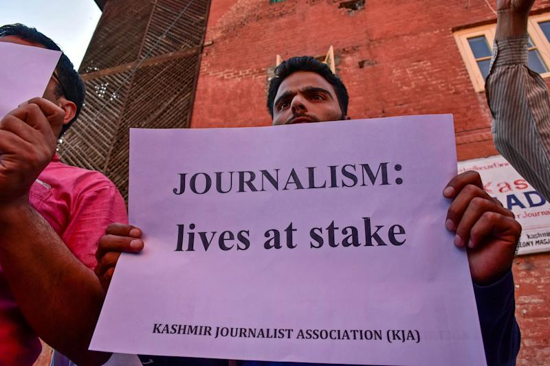 A Kashmiri journalist holds a placard during a protest against the continuous detention of Aasif Sultan. (Photo: Saqib Majeed/SOPA Images/LightRocket via Getty Images)