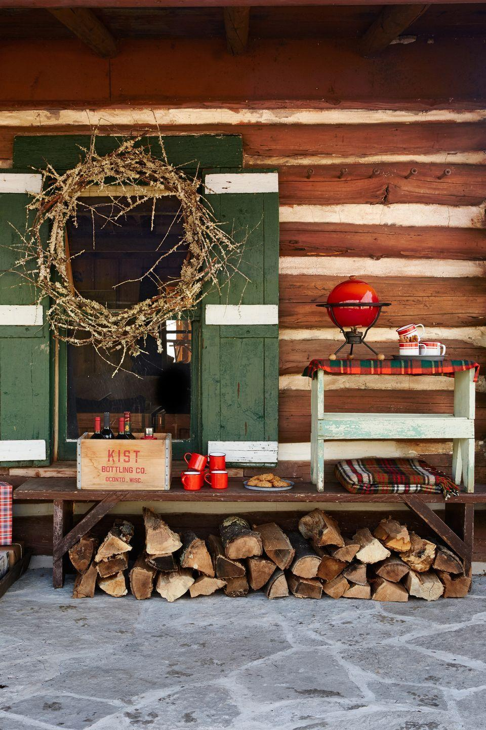 """<p>Made of moss- and lichen-covered twigs, the wreath sets an unfussy tone for visitors. Mulled wine, served from a 1960s Danish muller <em>(right) </em>adds to the warm welcome of this <span>cozy cabin</span>.</p><p><a class=""""link rapid-noclick-resp"""" href=""""https://www.amazon.com/s/ref=nb_sb_noss_1?url=search-alias%3Dgarden&field-keywords=grapevine+wreath&rh=n%3A1055398%2Ck%3Agrapevine+wreath&tag=syn-yahoo-20&ascsubtag=%5Bartid%7C10050.g.1247%5Bsrc%7Cyahoo-us"""" rel=""""nofollow noopener"""" target=""""_blank"""" data-ylk=""""slk:SHOP GRAPEVINE WREATHS"""">SHOP GRAPEVINE WREATHS</a><br></p>"""