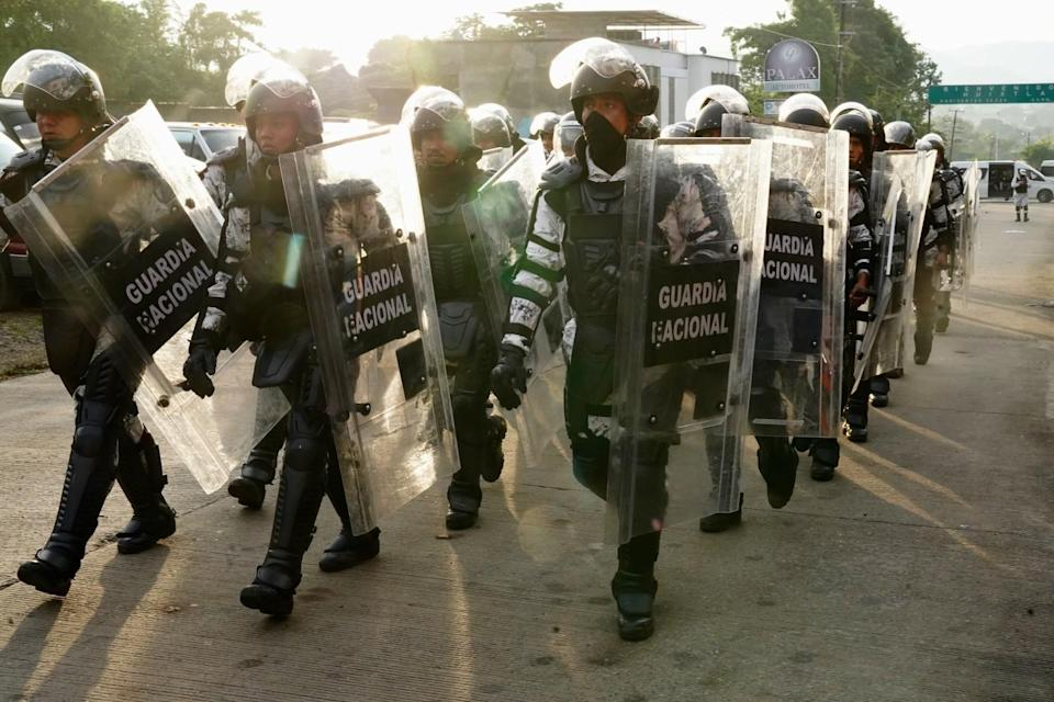 Uniformed people with helmets and shields walk in a group.