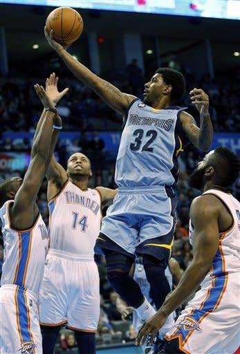 Memphis Grizzlies guard O.J. Mayo (32) shoots between Oklahoma City Thunder guard Daequan Cook (14) and guard James Harden, right, in the second quarter of an NBA basketball game in Oklahoma City, Friday, Feb. 3, 2012. (AP Photo/Sue Ogrocki)
