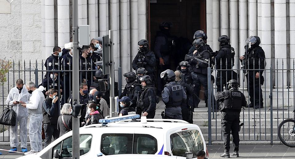 French police officers stand at the entrance of the Notre Dame Basilica church in Nice following a knife attack.