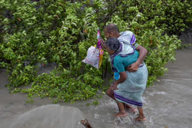 """DAKOP, KHULNA, BANGLADESH - 2020/05/20: A man with his old mother walks through water after crosses the river by boat immediately before Cyclone Amphan hits Bangladesh costal area in Khulna. Authorities have scrambled to evacuate low lying areas in the path of Amphan, which is only the second """"super cyclone"""" to form in the northeastern Indian Ocean since records began. (Photo by K M Asad/LightRocket via Getty Images)"""