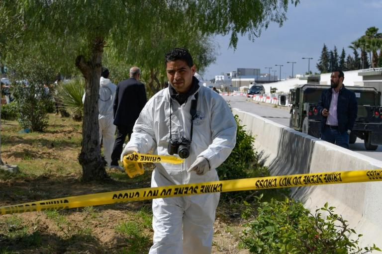 A forensic expert seals off the scene of the explosion near the US embassy in Tunis