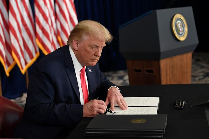 President Donald Trump signs executive actions at his golf resort in Bedminster, New Jersey, on Aug. 8, 2020.