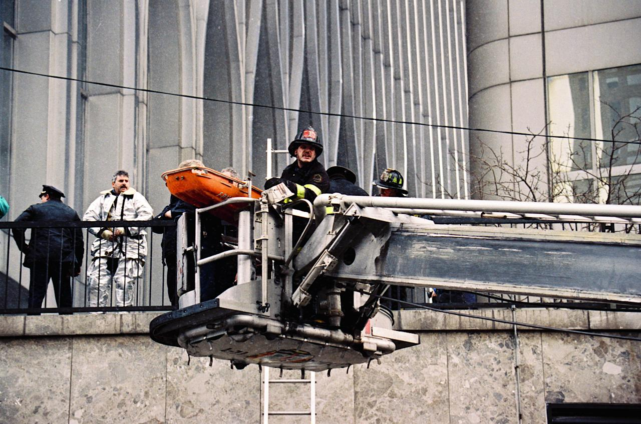 FILE - In this file photo of Feb. 26, 1993, firefighters in a cherry picker remove an explosion victim on a gurney outside one of the World Trade Center's twin towers in New York, after an explosion rocked the complex. Twenty years ago a group of terrorists blew up explosives in an underground parking garage under one of the towers, killing six people and ushering in an era of terrorism on American soil. (AP Photo/Alex Brandon, File)
