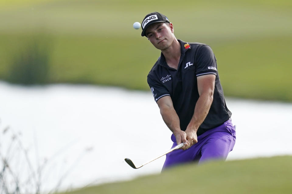 Viktor Hovland of Norway tries but fails to hit onto the 18th green from an embankment near the water during the third round of the PGA Zurich Classic golf tournament at TPC Louisiana in Avondale, La., Saturday, April 24, 2021. (AP Photo/Gerald Herbert)