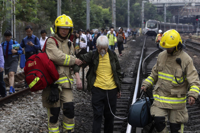 Firefighters help an elderly woman as commuters walk on the railway after their train service is disrupted by pro-democracy protesters in Hong Kong, Tuesday, Nov. 12, 2019. Protesters disrupted the morning commute in Hong Kong on Tuesday after an especially violent day in the Chinese city that has been wracked by anti-government protests for more than five months. (AP Photo)