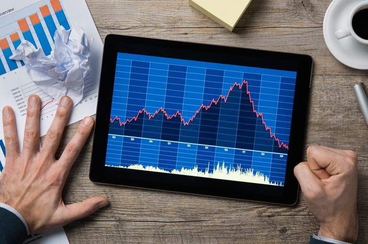 An angry fist pounding a table as a falling stock chart displays on a tablet below.