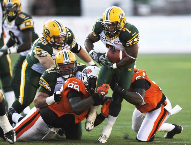 B.C. Lions Jabar Westerman, 99, and Khreem Smith, right, tackle the Edmonton Eskimos Hugh Charles, 7, as Eskimos' Kyle Koch, 61, defends, during the second quarter of CFL pre-season football action in Edmonton, Alta., Thursday, June 21, 2012. THE CANADIAN PRESS/John Ulan
