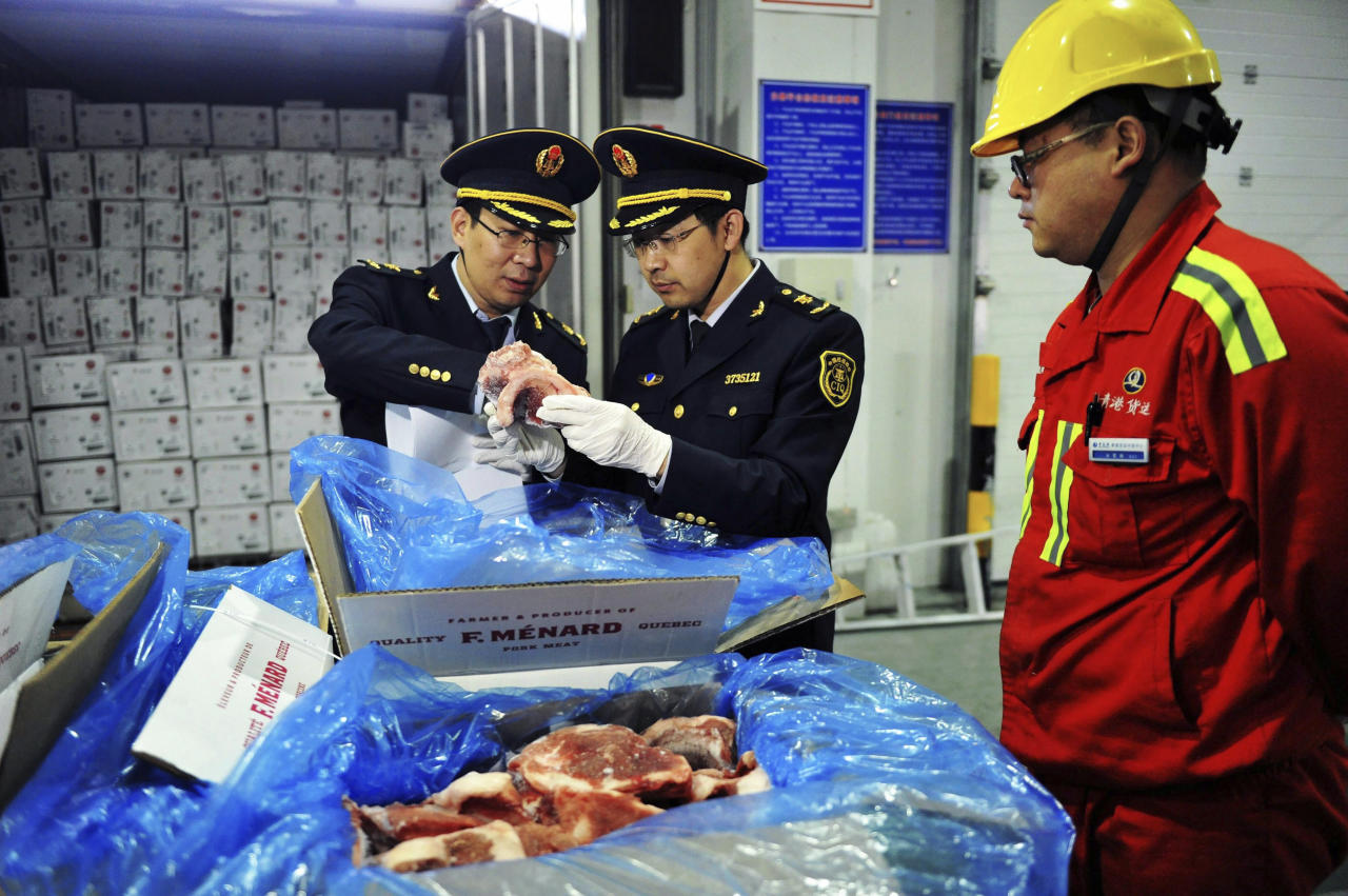 In this April 13, 2017, photo, a warehouse worker watches as government inspectors check imported frozen pork in Qingdao in eastern China's Shandong province. China announced a list of U.S. goods including pork, apples and steel pipe on Friday, March 23, 2018, that it said may be hit with higher import duties in response to President Donald Trump's tariff hike on steel and aluminum. (Chinatopix via AP)