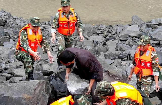 <p>Rescue personnel work at the site of a landslide that destroyed some 40 households, where more than 100 people are feared to be buried, according to local media reports, in Xinmo Village, China, June 24, 2017. (Photo: Stringer/Reuters) </p>