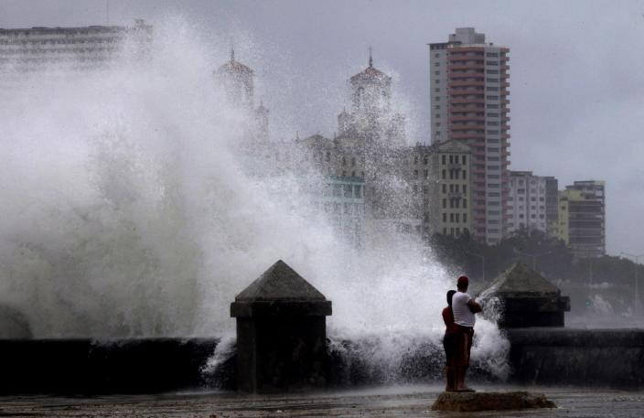 Waves pound the boardwalk, the Malecon, during the passing of Tropical Storm Isaac in Havana Cuba, Sunday, Aug. 26, 2012. The hurricane center said the storm, which was swirling north of the central coast of Cuba in the pre-dawn hours, was expected to be near or over the Florida Keys sometime later Sunday or Sunday night. (AP Photo/Ramon Espinosa)