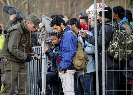 Austrian soldier fixes the fence as migrants wait to cross the border into Spielfeld in Austria from the village of Sentilj, Slovenia