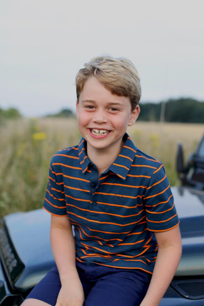 Prince George, who just turned eight, is pictured sitting on the bonnet of a Land Rover Defender wearing a striped polo.
