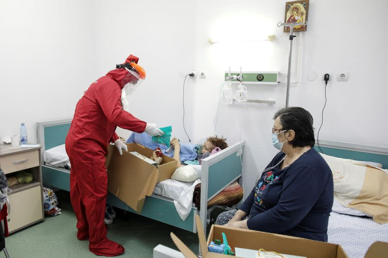 Ionut Ivan, a 40-year-old nurse, dressed in red Personal Protective Equipment (PPE) opens a box with sweets and fruits for one of the patients, in Bucharest