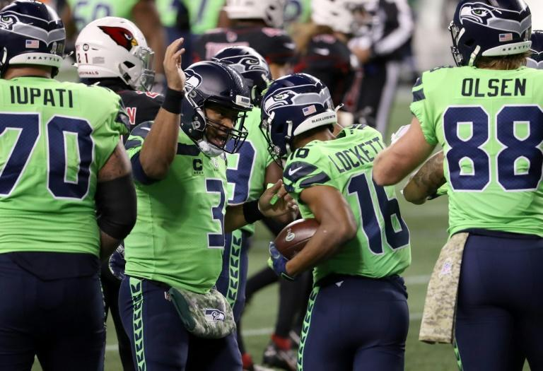 Seattle quarterback Russell Wilson, 3, congratulates teammate Tyler Lockett, 16, after Lockett caught a pass for a touchdown in a battle for first place in the division between the Seahawks and the Arizona Cardinals in Seattle, Washington