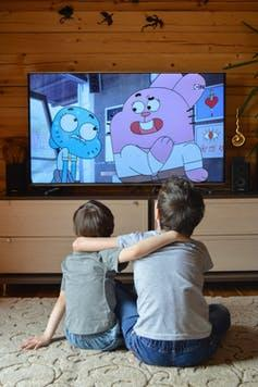 Two children sitting on the floor watching a cartoon.