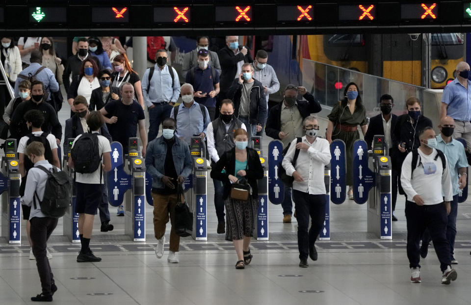 People wear face masks to curb the spread of coronavirus during the morning rush hour at Waterloo train station in London, Wednesday, July 14, 2021. (AP Photo/Matt Dunham)