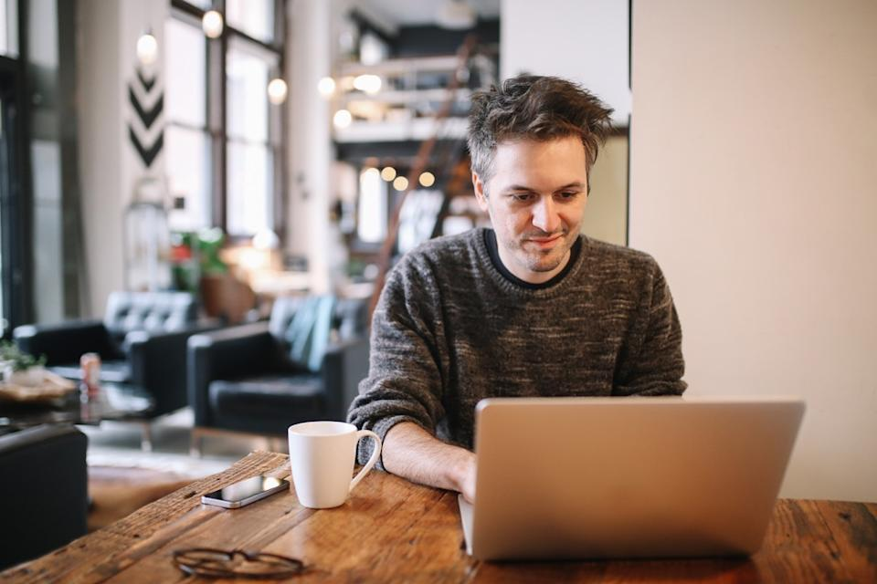 Young man sitting at the desk, doing an IT work or just casually browsing the web, checking e-mail, using social networks. He is having a cup of coffee, sitting in the living room of his Los Angeles loft apartment.
