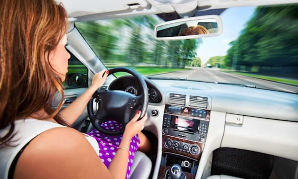 Young woman driving car. Fast motion effect.