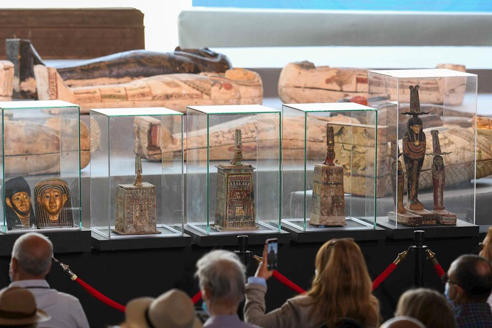 A picture shows statues and funerary masks on display during the unveiling of an ancient treasure trove of more than a 100 intact sarcophagi, at the Saqqara necropolis 30 kms south of the Egyptian capital Cairo, on November 14, 2020. - Egypt announced the discovery of an ancient treasure trove of more than a 100 intact sarcophagi, the largest such find this year. The sealed wooden coffins, unveiled on site amid fanfare, belonged to top officials of the Late Period and the Ptolemaic period of ancient Egypt. They were found in three burial shafts at depths of 12 metres (40 feet) in the sweeping Saqqara necropolis south of Cairo. (Photo by Ahmed HASAN / AFP) (Photo by AHMED HASAN/AFP via Getty Images)
