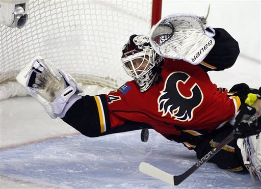 Calgary Flames goalie Miikka Kiprusoff, from Finland, dives on the puck during the second period of an NHL hockey game against the Columbus Blue Jackets, Friday, March 29, 2013, in Calgary, Alberta. (AP Photo/The Canadian Press, Jeff McIntosh)