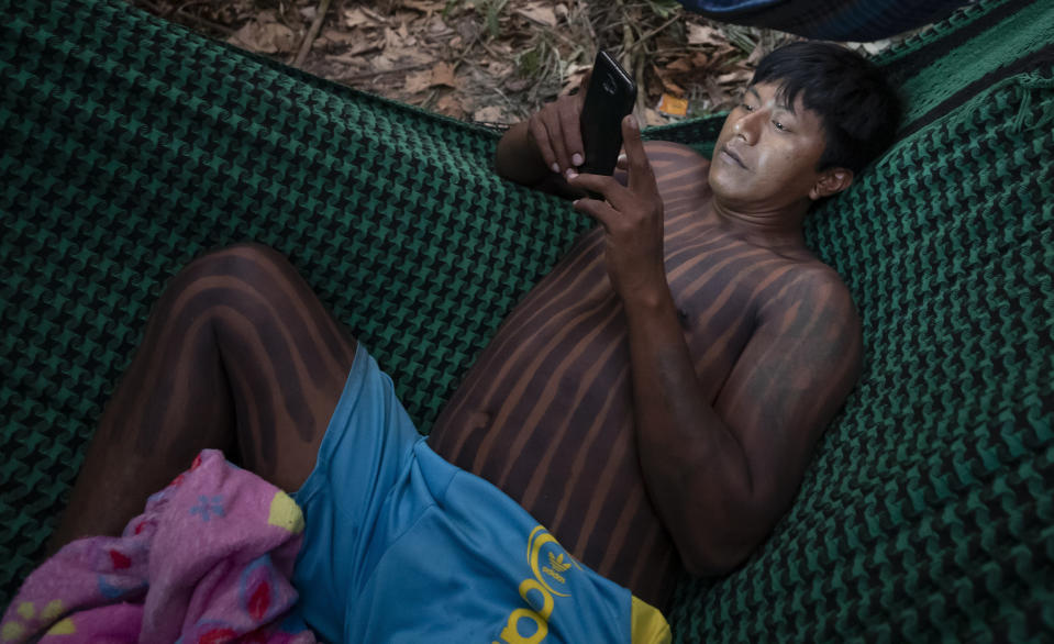 FILE - In this Aug. 19, 2020 file photo, a Kayapo Indigenous man checks his cellphone while resting in a hammock near Novo Progresso, Para state, Brazil. Although Indigenous communities have gained greater access to technology and the internet in recent years, information often arrives in a very distorted way. That means vaccine skepticism has gained even more traction in a place where it is sorely needed amid a crushing wave of infections and the spread of a worrisome variant of COVID-19. (AP Photo/Andre Penner, File)