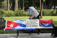 A Cuban man arranges a Cuban flag next to a Venezuelan national flag during a small demonstration in Alameda Park against the participation of Venezuela's President Nicolas Maduro in the Community of Latin American and Caribbean States, CELAC, summit in Mexico City, Saturday, Sept. 18, 2021. CELAC has only existed for 10 years and is more left-leaning, having remained on good terms with countries including Cuba, Venezuela and Nicaragua. (AP Photo/Ginnette Riquelme)
