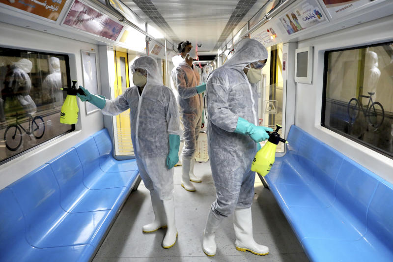 Workers disinfect subway trains against coronavirus in Tehran, Iran, in the early morning of Wednesday, Feb. 26, 2020. Iran's government said Tuesday that more than a dozen people had died nationwide from the new coronavirus, rejecting claims of a much higher death toll of 50 by a lawmaker from the city of Qom that has been at the epicenter of the virus in the country. (AP Photo/Ebrahim Noroozi)