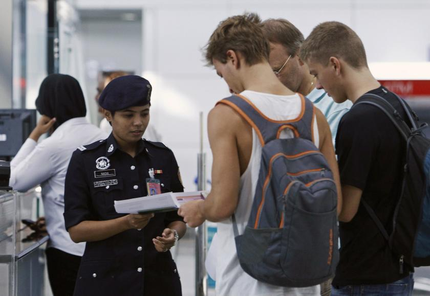 A police officer checks the travel documents and passports of passengers at Kuala Lumpur International Airport in Sepang March 9, 2014. — Reuters pic