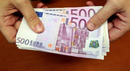 FILE PHOTO: A bank employee holds a pile of 500 euro notes  at a bank branch in Madrid January 13, 2011.  REUTERS/Andrea Comas/File Photo