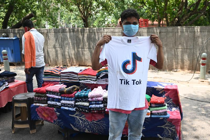 A garment street vendor poses for a picture in front of his stall with a t-shirt with the logo of the social media video-sharing application Tik Tok in New Delhi on June 30, 2020. / Credit: SAJJAD HUSSAIN/AFP/Getty